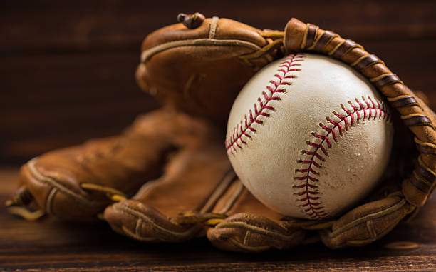 Leather baseball glove and ball on a wooden bench